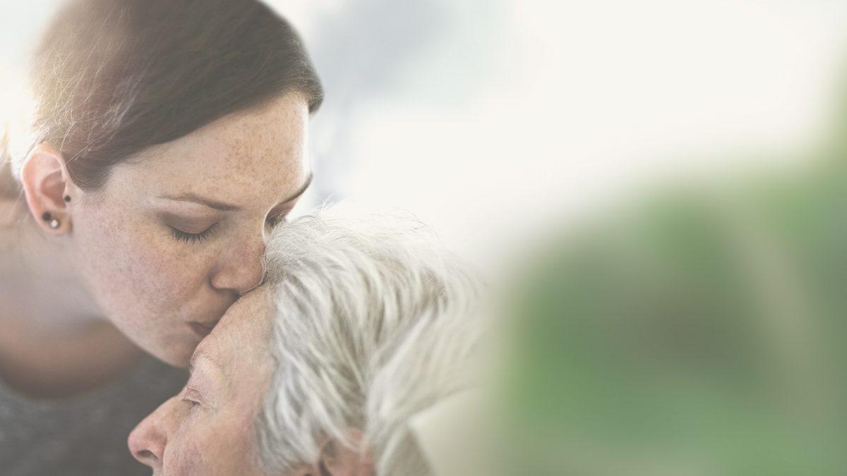 Mujer dándole un beso en la frente a su madre